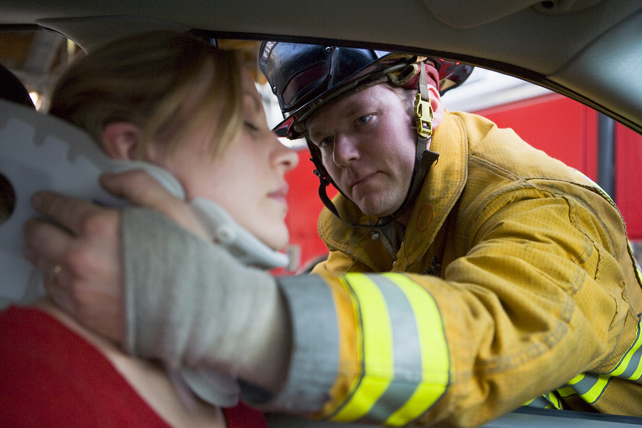 fireman helping injured woman in car accident with neck brace
