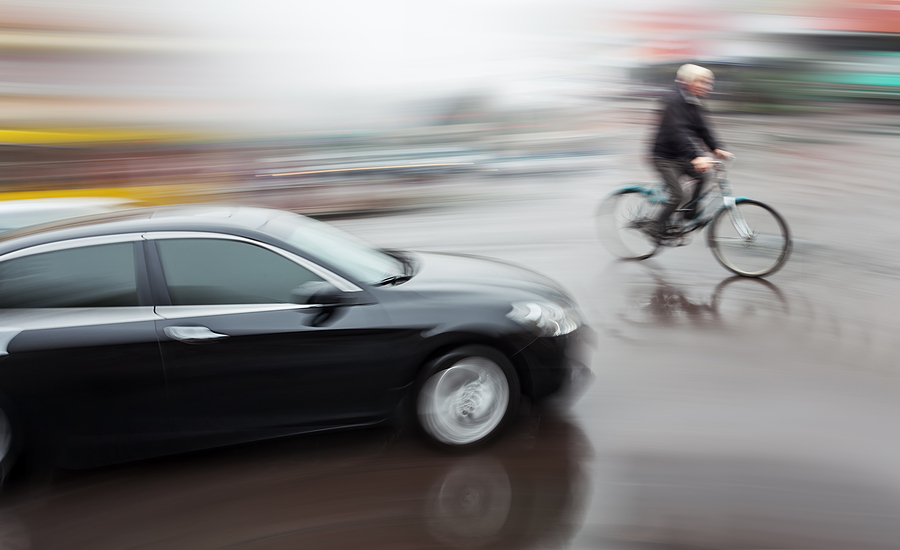 blurry bicyclist dangerously crosses in front of moving car
