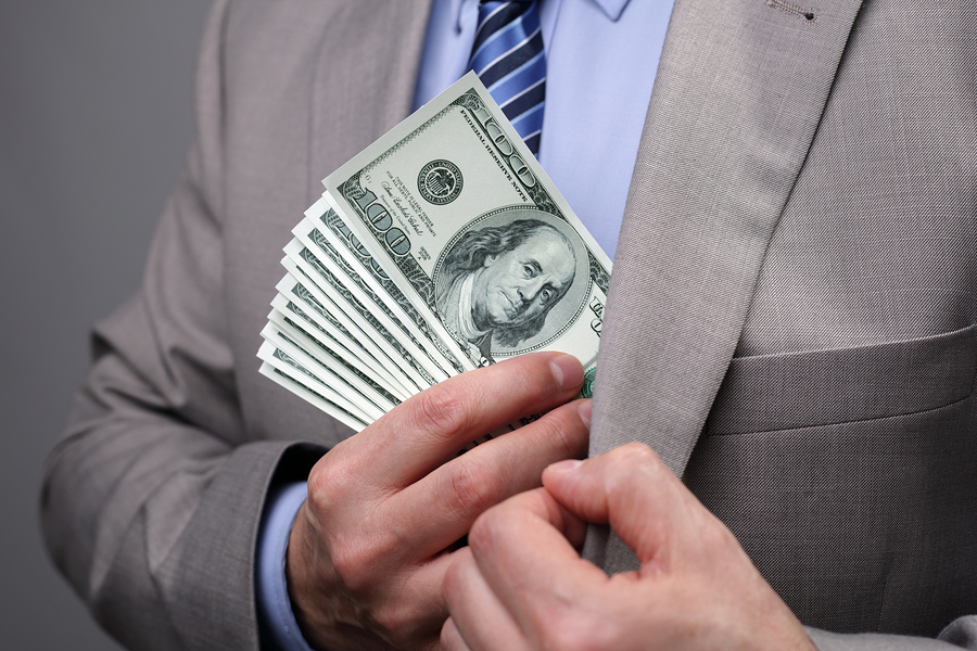 Man putting money in suit jacket pocket concept for corruption,
