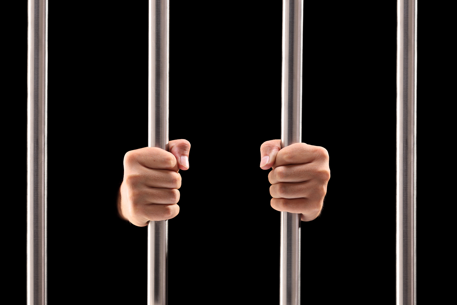 Male hands holding prison bars isolated on black background